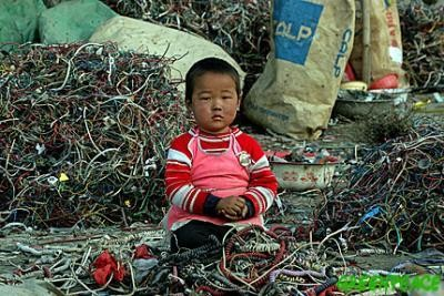 A Chinese child sits amongst a pile of wires and e-waste. Children can often be found dismantling e-waste containing many hazardous chemicals known to be potentially very damaging to children's health.