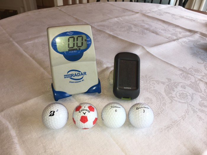 Figure 1. The four golf balls  I tested, my swing speed radar unit, and my GPS unit.